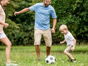 Barn och föräldrar spelar fotboll